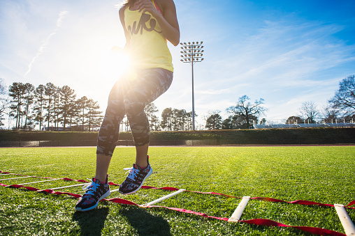 Neck down view of female athlete training with agility ladder on sports field